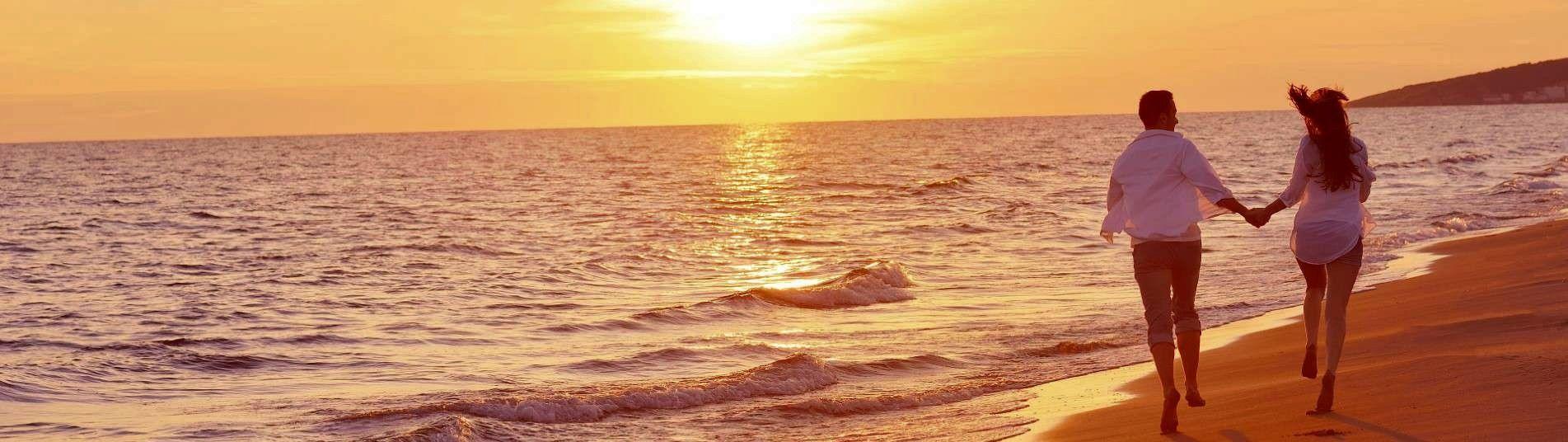 Couple sur la plage au soleil couchant